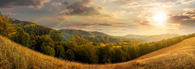 mountainous countryside at sunset. beautiful panorama of carpathians. valley of borzhava ridge under the rainbow in evening light. clouds on the sky. sunny weather