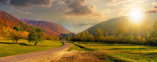 road winding through the country valley at sunset. wonderful autumn landscape in mountains in evening light. forest on hills in colorful foliage. sunny weather with fluffy clouds on the sky