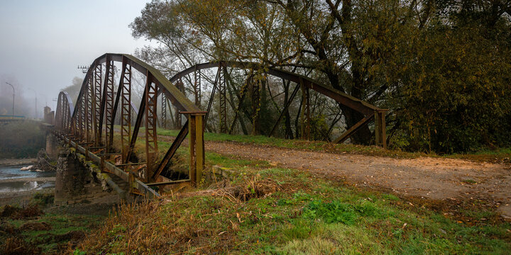 abandoned metal bridge in morning fog. dangerous construction in autumnal countryside scenery at sunrise