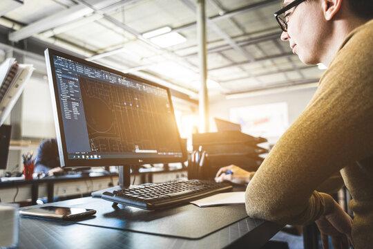 Engineer designer working on desktop computer in factory