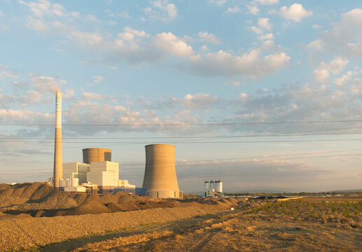 Chimney of power station on field under blue sky