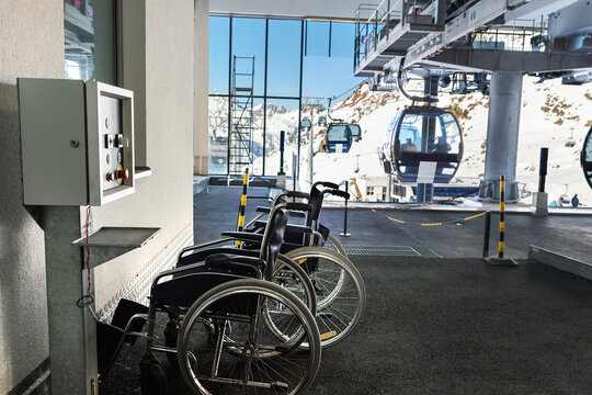 Many empty wheelchairs prepared for disabled people at station of cabin gondola ski lift at mountain alpine luxury austrian winter resort. Handicapped person friendly care service