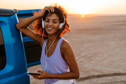 Image of happy african american woman using headphones and cellphone