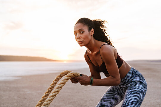 Image of african american sportswoman working out with battle ropes