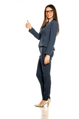 beautiful young smiling business woman in pants and jacket showing thumbs up