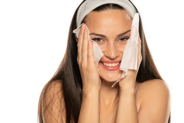 young smiling woman cleaning her face with wet tissues