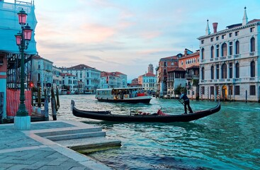 Scenery of romantic Venice at sunset, with view of a gondolier steering his ferry gondola by a pier, a vaporetto waterbus approaching from behind and beautiful old buildings by the Grand Canal