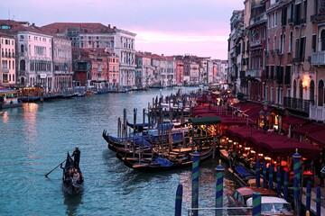 Scenery of Venice in blue dusk, with tourists riding in gondolas & water buses on Grand Canal and ferry boats parking by restaurants & bars, a view from Rialto Bridge (faded color, nostalgic effect)