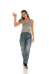 Young Indian woman in jeans walking and waving hand