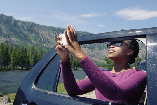 Black young woman taking photos in Yellowstone from car