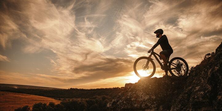Man on mountain bike against sundown sky