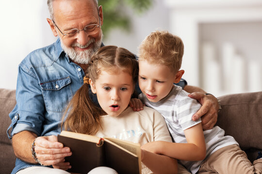 Grandfather reading book to children.
