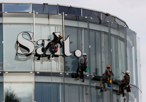 Climbers clean the logo and windows of the building of phone operator Salt. in Renens