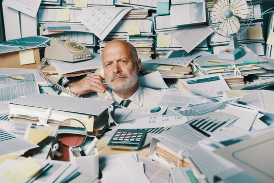 Stressed businessman overwhelmed by work
