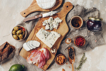 Set of cheese, hamon, honey, green olives, nuts and spices on rustic wooden board