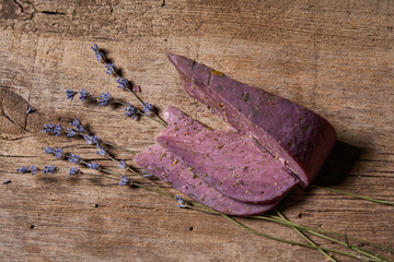 Lavender cheese with bunch of fresh lavender flowers on rough wooden planks