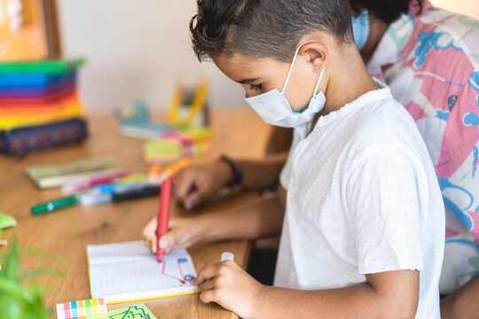 Boy child painting in preschool classroom wearing face protective mask - Back to school during coronavirus outbreak concept - Focus on ear