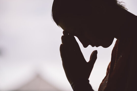 silhouette of peaceful woman in prayer position