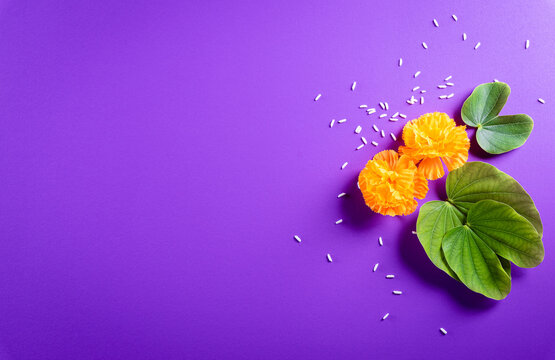 Happy Dussehra. Yellow flowers, green leaf and rice on purple pastel background. Dussehra Indian Festival concept.