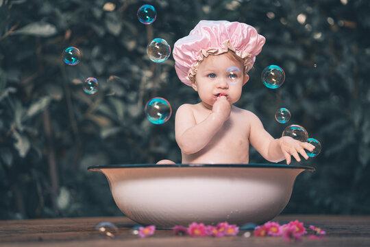 Baby Mädchen mit rosa Duschhaube sitzt in einer alten Waschschüssel im Garten und Seifenblasen Var. 4