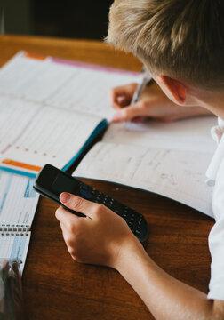 Tween boy doing maths homework with a calculator.