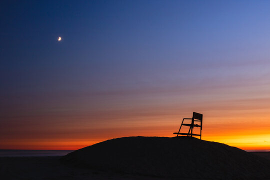 Sunset and crescent moon over a beach, with a lifeguard tower silhouette. Long Beach New York