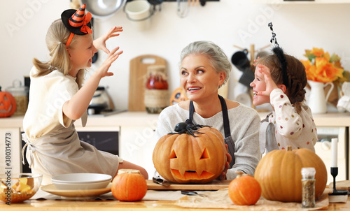 Granddaughters scaring grandmother during Halloween celebration.