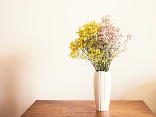 Dried pink and yellow flowers in white vase against white wall. Home interior autumn decor