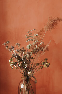 Beautiful autumn bouquet of dried flowers of brown shades in a glass vase on a red-orange vintage background
