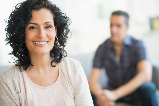 Portrait of smiling woman with man in background