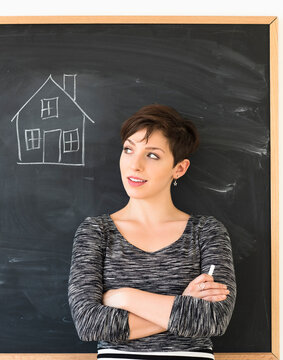 Woman in front of blackboard with house drawing