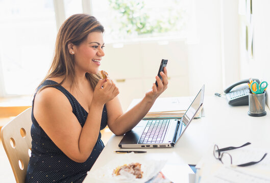 Woman eating croissant and using mobile phone in office