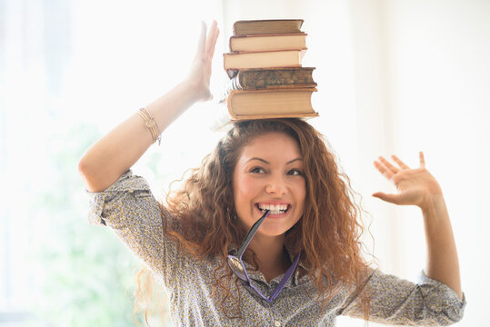 Portrait of woman with books on top of head