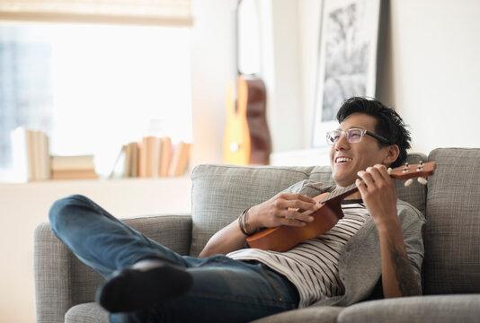 Man sitting on sofa and playing ukulele