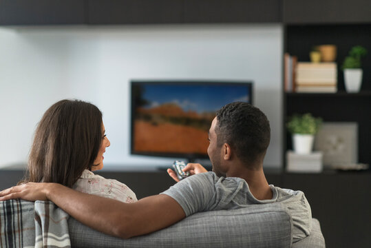 Couple sitting in living room and watching TV