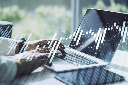 Abstract creative financial graph with hand typing on laptop on background, financial and trading concept. Multiexposure