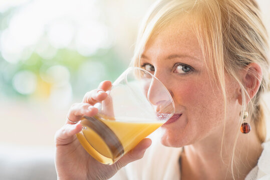 Woman sitting in living room and drinking orange juice