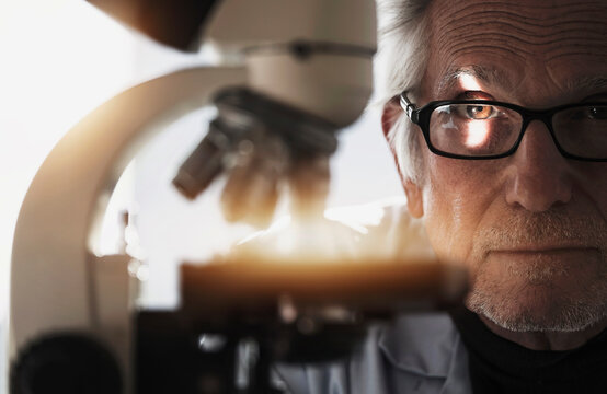 Close up of man behind microscope