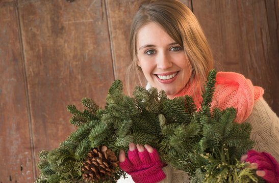 Portrait of young woman with christmas wreath in hands