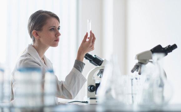 Female lab technician examining liquid in test tube