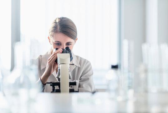 Female lab technician analyzing sample through microscope