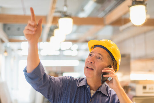 Architect in hardhat talking on mobile phone