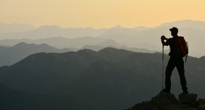 silhouette of the tired mountaineer watching the mountains