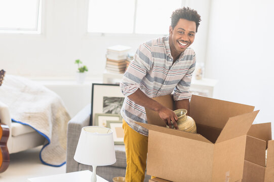 Man packing decors into cardboard box
