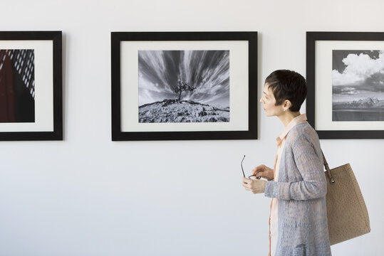 Woman watching photographs in art gallery