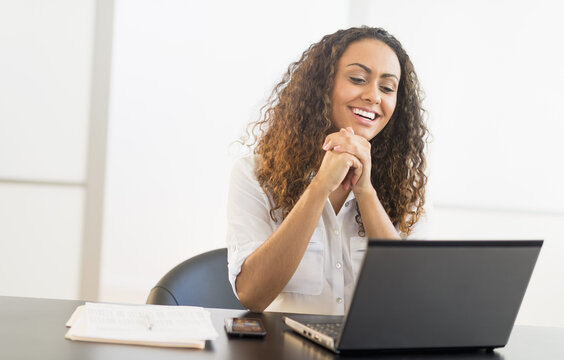 Office worker sitting by desk with laptop
