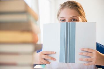 Teenage girl (12-13) hiding face behind book