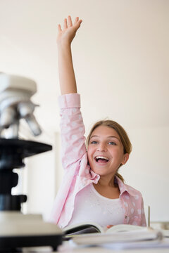 Girl (12-13) raising hand to answer question at school