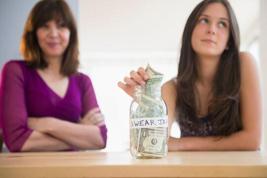 Teenage girl (14-15) putting money in swear jar