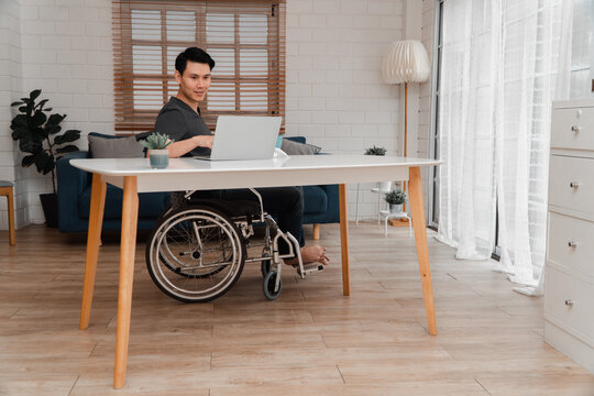 Happy disabled Asian man sitting in a wheelchair And working with computer at home, The concept of Technologies for the convenience of people with disabilities.